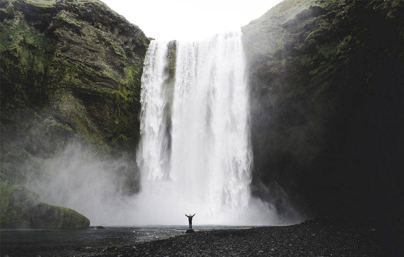 picture of a person standing in front of a waterfall illustrating the white paper about circular economy
