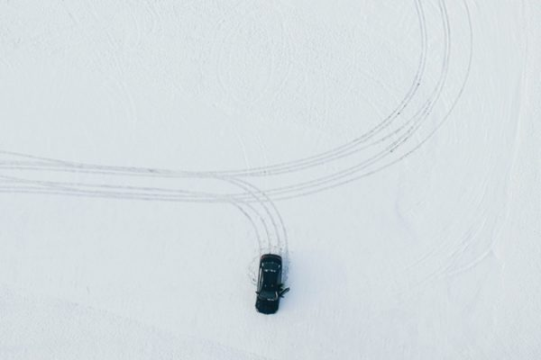 picture from above of a car driving in the snow visualizing the blog article about the interview with sebastian gschwill